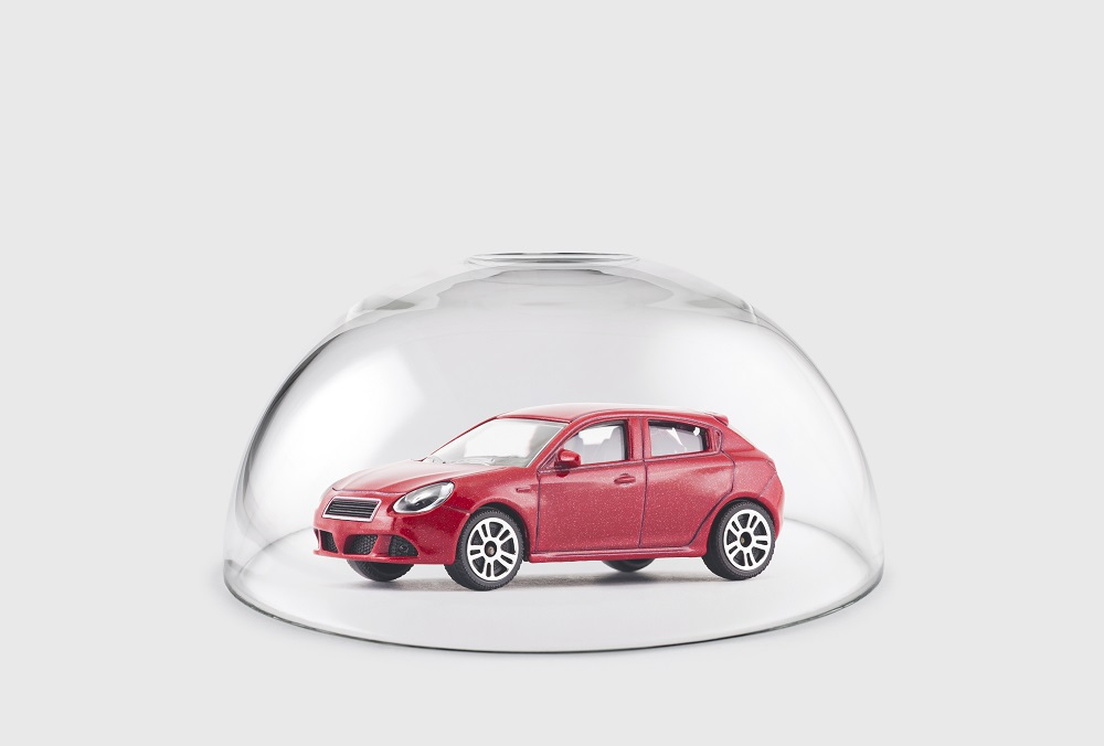 A red hatchback style toy car under a glass dome against a gray background, positing the question, Do I Need Personal Injury Protection Car Insurance in Philadelphia?