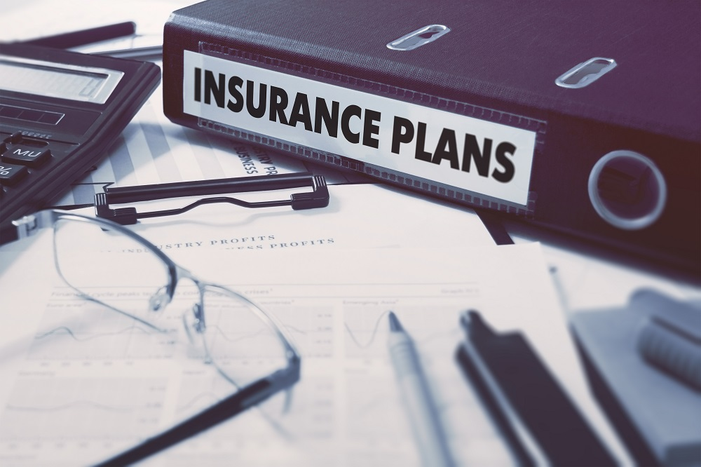 A cluttered desk with a big, dark colored binder labeled insurance, positing the question, What is personal injury insurance in Philadelphia and PA?