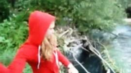 La joven se ríe cuando arroja uno por uno al río a los seis cachorros vivos. (Foto: captura vídeo)