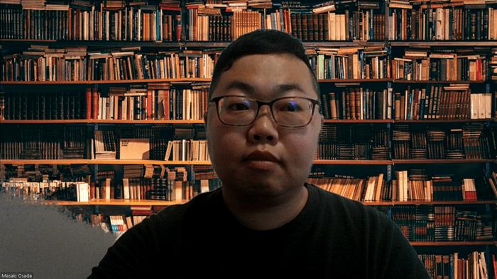 賢者の様な本棚をバックに
