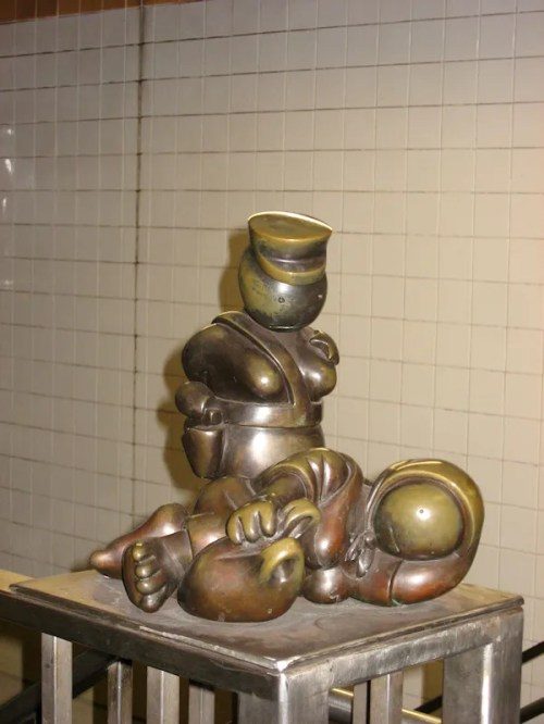 Photo of bronze guard and sleeping woman at 8th Ave subway station in NY, taken by Joana Miranda