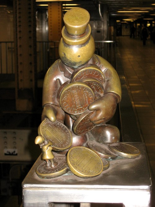 Bronze statue of worker giving little person some money, taken by Joana Miranda
