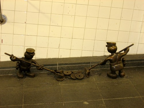 Photo of two bronze workman sweeping up the subway, taken by Joana Miranda