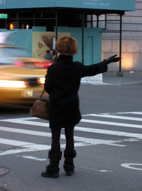 Photo of a lady in a funny furry hat hailing a cab in NY City, taken by Joana Miranda