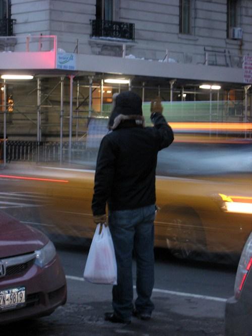 Photo of man in Fargo-style hat hailing a cab in NY City, taken by Joana Miranda