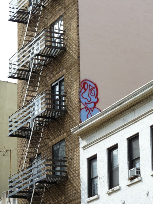 Photo of blue and red graffiti face on wall in Chinatown, taken by Joana Miranda