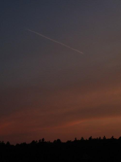 Photo of sunset with plane streaking across the sky, taken by Joana Miranda