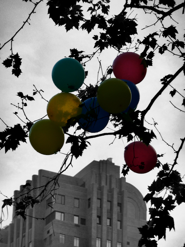 Black and white photo of Art Deco building with colored balloons, taken by Joana Miranda
