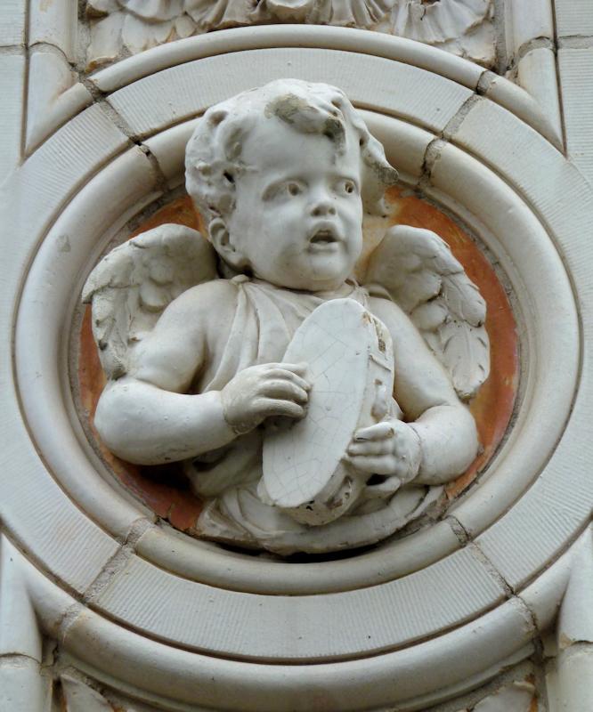Photo of stone frieze of angel singing and playing a tambourine, taken by Joana Miranda
