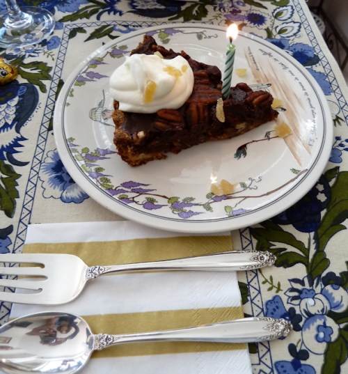 Photo of slice of chocolate pecan ginger tart with whipped cream, crystallized ginger and candle, taken by Joana Miranda