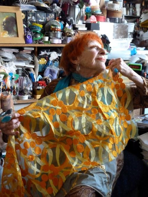 Photo of Ilona Royce Smithkin holding orange fabric, taken by Joana Miranda