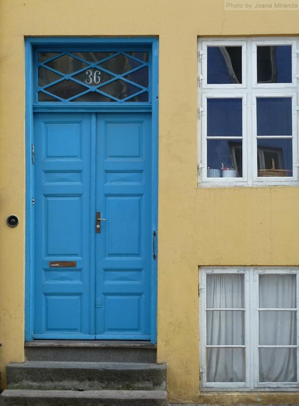 Photo of blue door and yellow wall in building in Copenhagen, Denmark. Photo by Joana Miranda