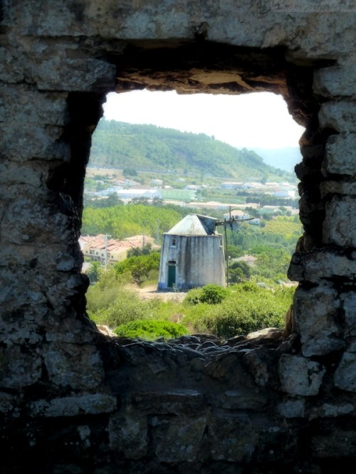 Windmill through a gap in the wall at Obidos