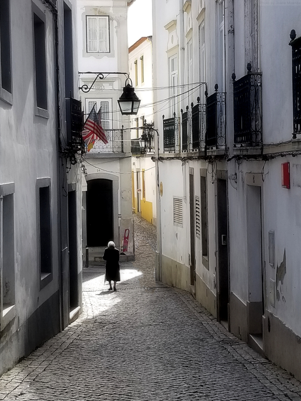 Little old lady walking down the street in Evora, Portugal