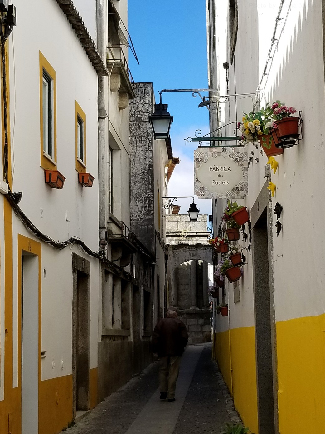 Photo of old man walking down a street in Evora, Portugal