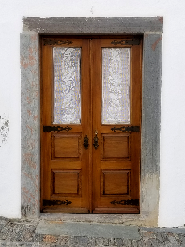 Photo of wooden door with white lace curtains in Monsaraz, Portugal
