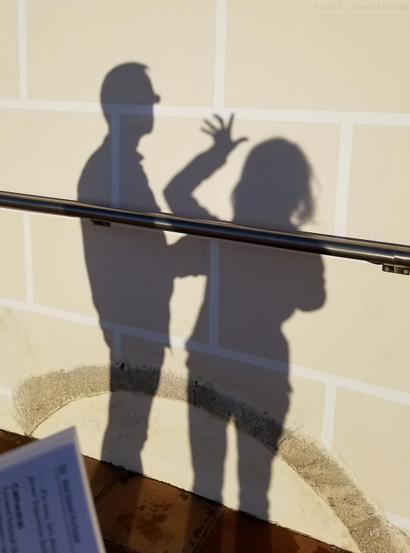 Photo of two shadows against a stone wall.