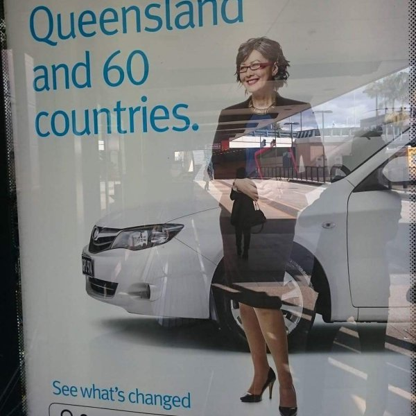 Asian female corporate standing in front of white car for E10 biofuel Queensland advertisement at a bus stop