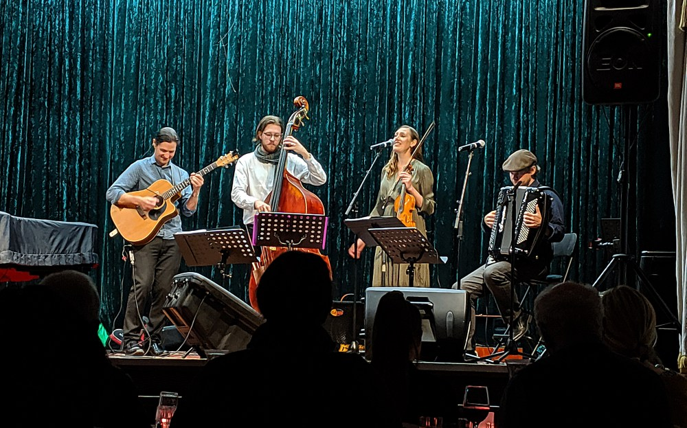 four acoustic musicians on a stage guitarist double bass violin accordion