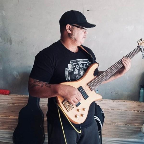 Man wearing baseball cap holding bass guitar