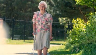 Elderly lady walking in a park with a walking stick