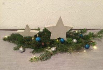2 Sterne aus Beton auf einem Tannenzweig als DIY Weihnachtsdeko aus Beton