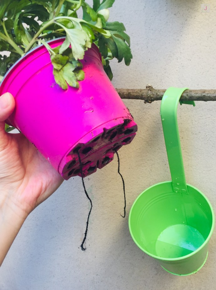 diy hanging flower decor - flower pot with yarn string on the bottom for watering