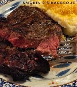 raised bite of juicy steak potato in background