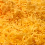 A pile of shredded sharp cheddar cheese.