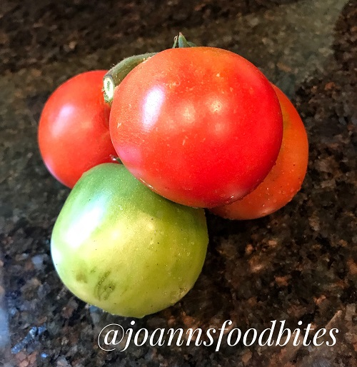 Three bright red tomatoes and one green tomato