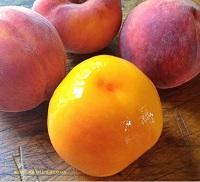 three whole peaches and one peeled peach