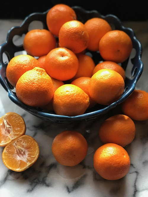 blue bowl of oranges