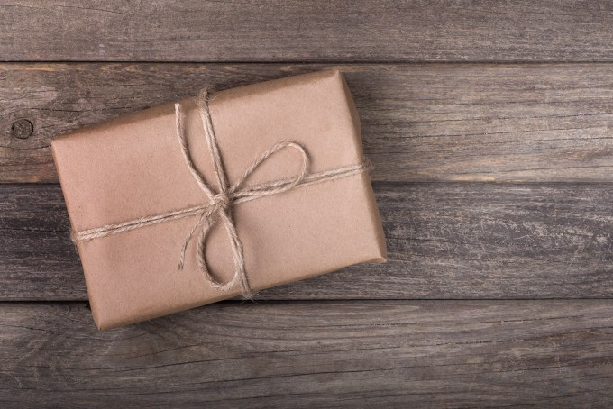 Single brown package tied with string on a wood background