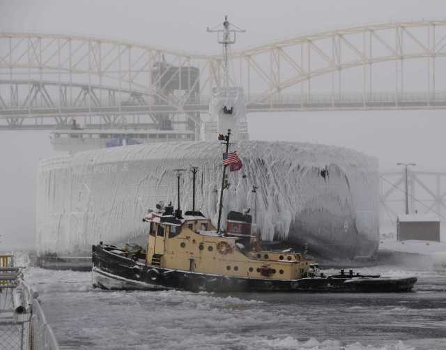 taken by Detroit District Employee, Carmen Paris. The Soo Area Office based tug Owen M. Frederick was breaking ice in and to the upper approach of the Poe Lock while the 1,000 footer M.V. Walter J. MC Carthy Jr. waits to lock down bound through the Poe Lock.