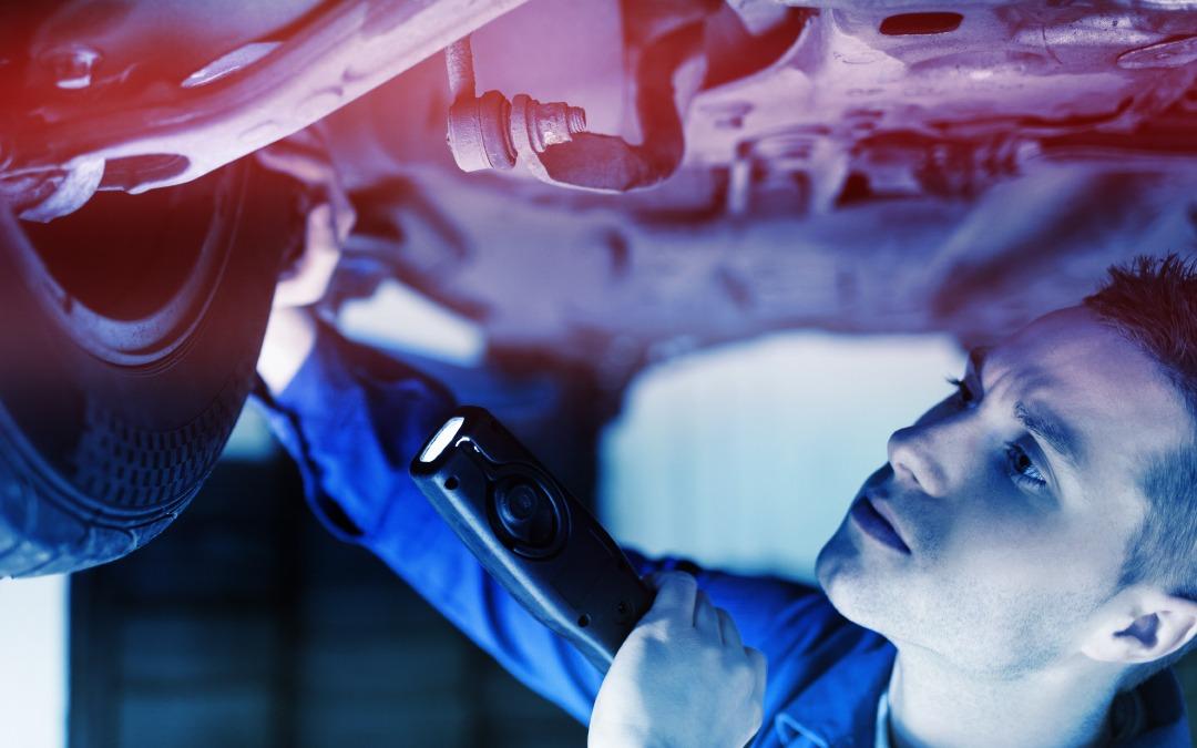 Mécanicien inspectant l'essieu intérieur d'un véhicule surélevé avec une lampe torche.