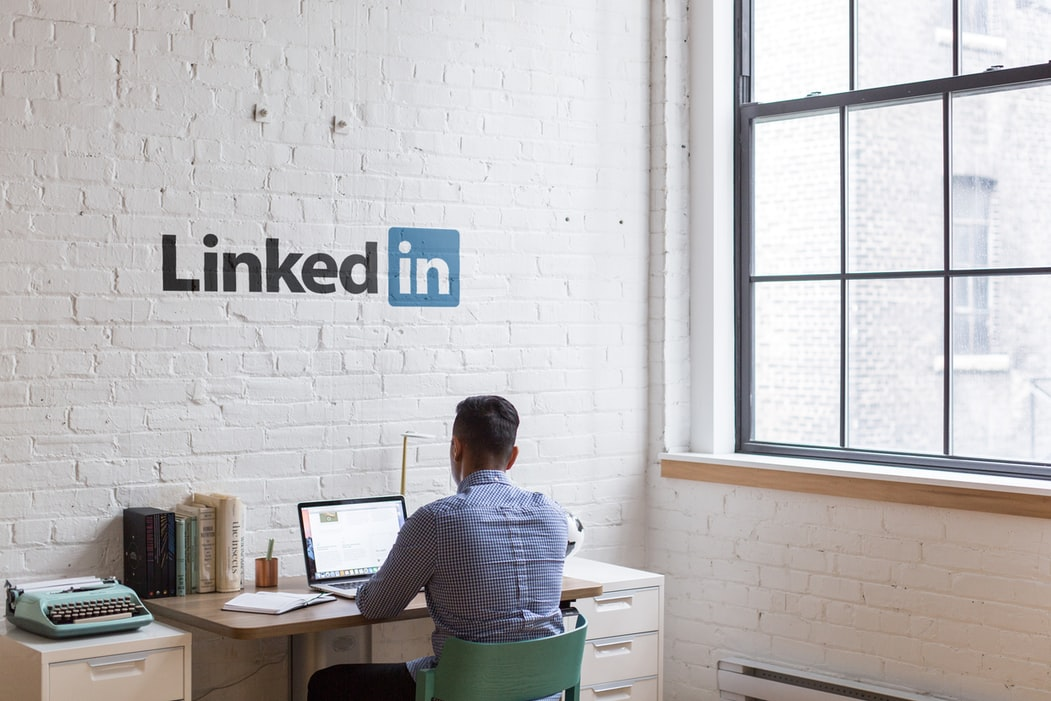 A man sat in an office with the LinkedIn logo on the wall. Maybe he's a LinkedIn digital marketing expert?