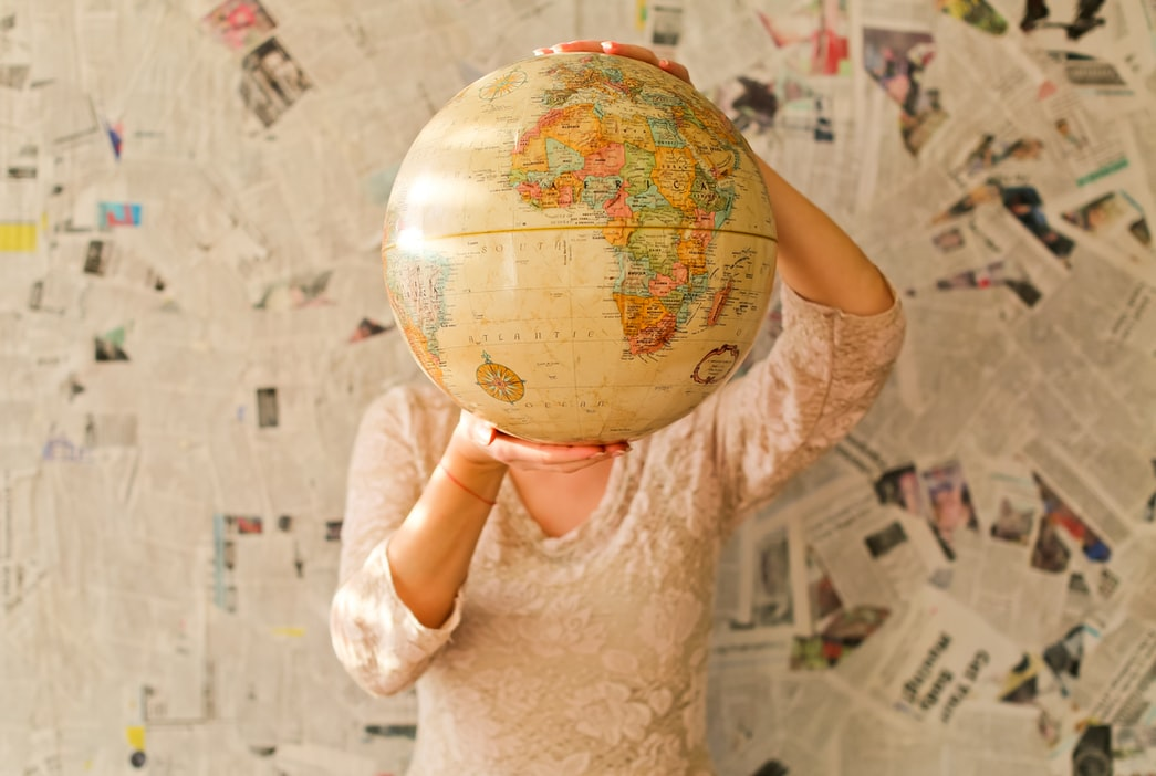 A lady holds a globe in front of a wall covered in newspapers. What are the top job boards in the world?