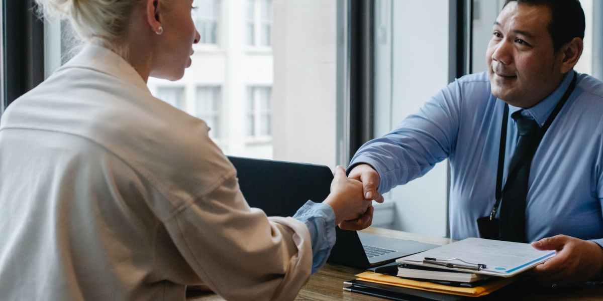 A male recruiter shakes hands with a female candidate in a job interview. maybe he found her application on a job site in this guide?