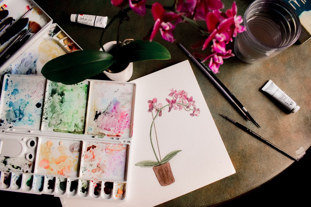 A colour palette and a watercolour painting of some flowers.