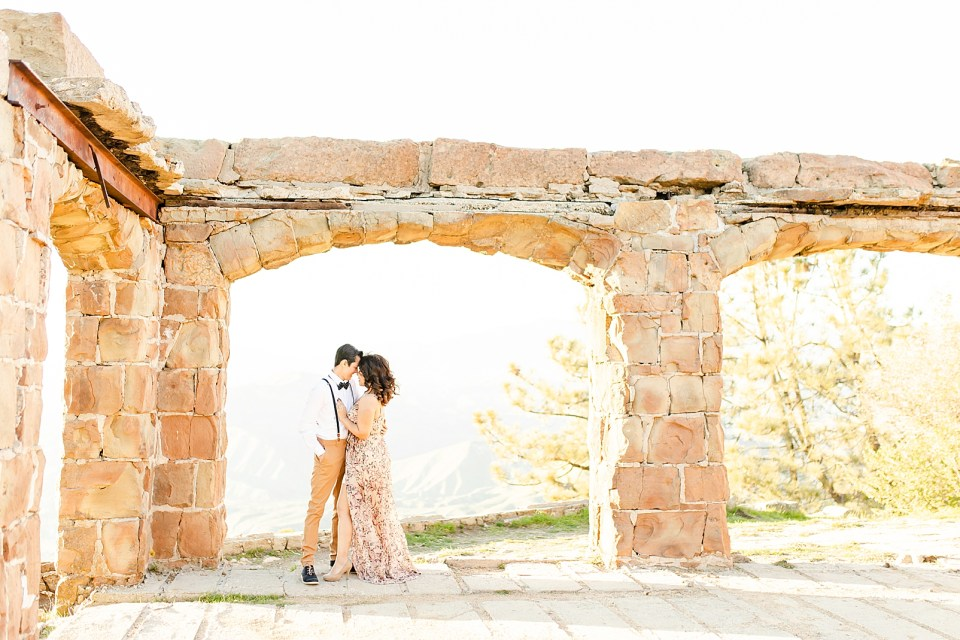 Breanna & Peter under the Knapp's Castle arches holding each other close. She is wearing a long light-colored flowy dress with floral print and he is wearing tan khakis and a white button up shirt with suspenders and black shoes.