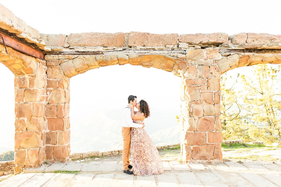 The couple sharing a kiss under the arch during their magical Knapp's Castle engagement session