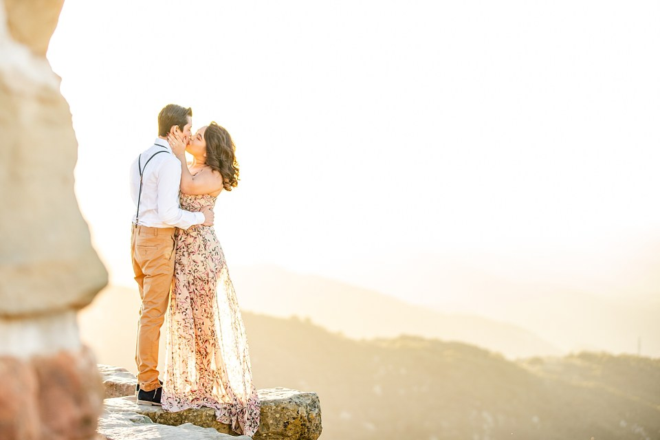 The couple sharing a kiss as the sunlight shines through her dress