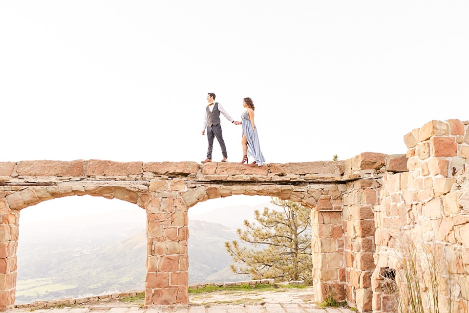 Peter leading Breanna by the hand while walking along the top of the arch during their magical Knapp's Castle engagement session