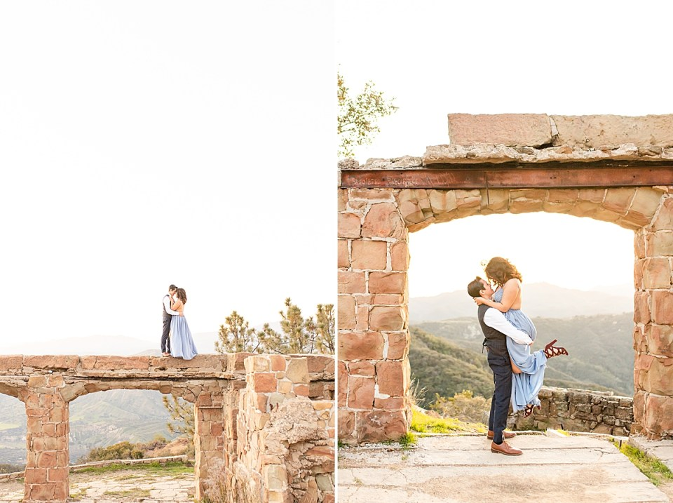 The couple holding each other close while in top of the arch at Knapp's Castle. And Peter lifting Breanna in the air slightly above his head as she looks down at him.