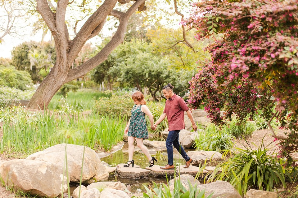 Danielle leading Ray across a small stream over some stones while holding hands.