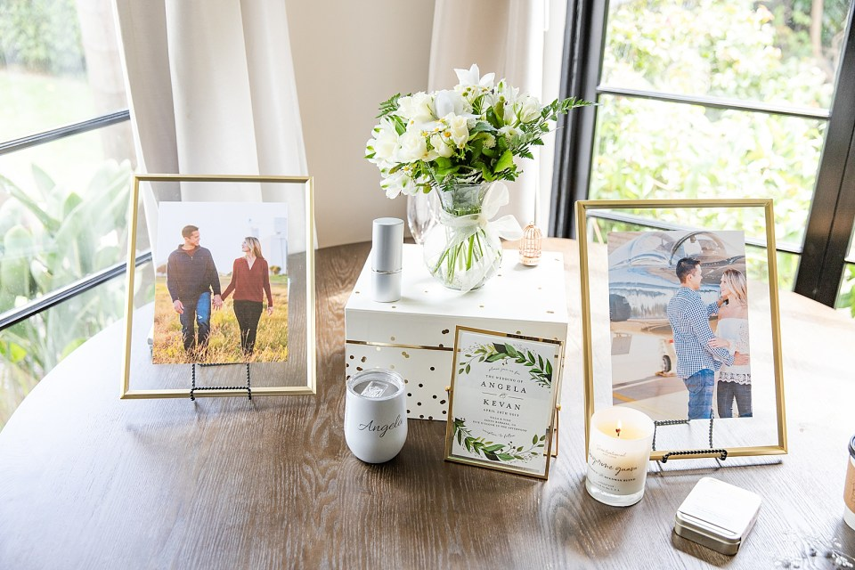 Two photos of the happy couple and their wedding invitations in frames on a table next to her bouquet.