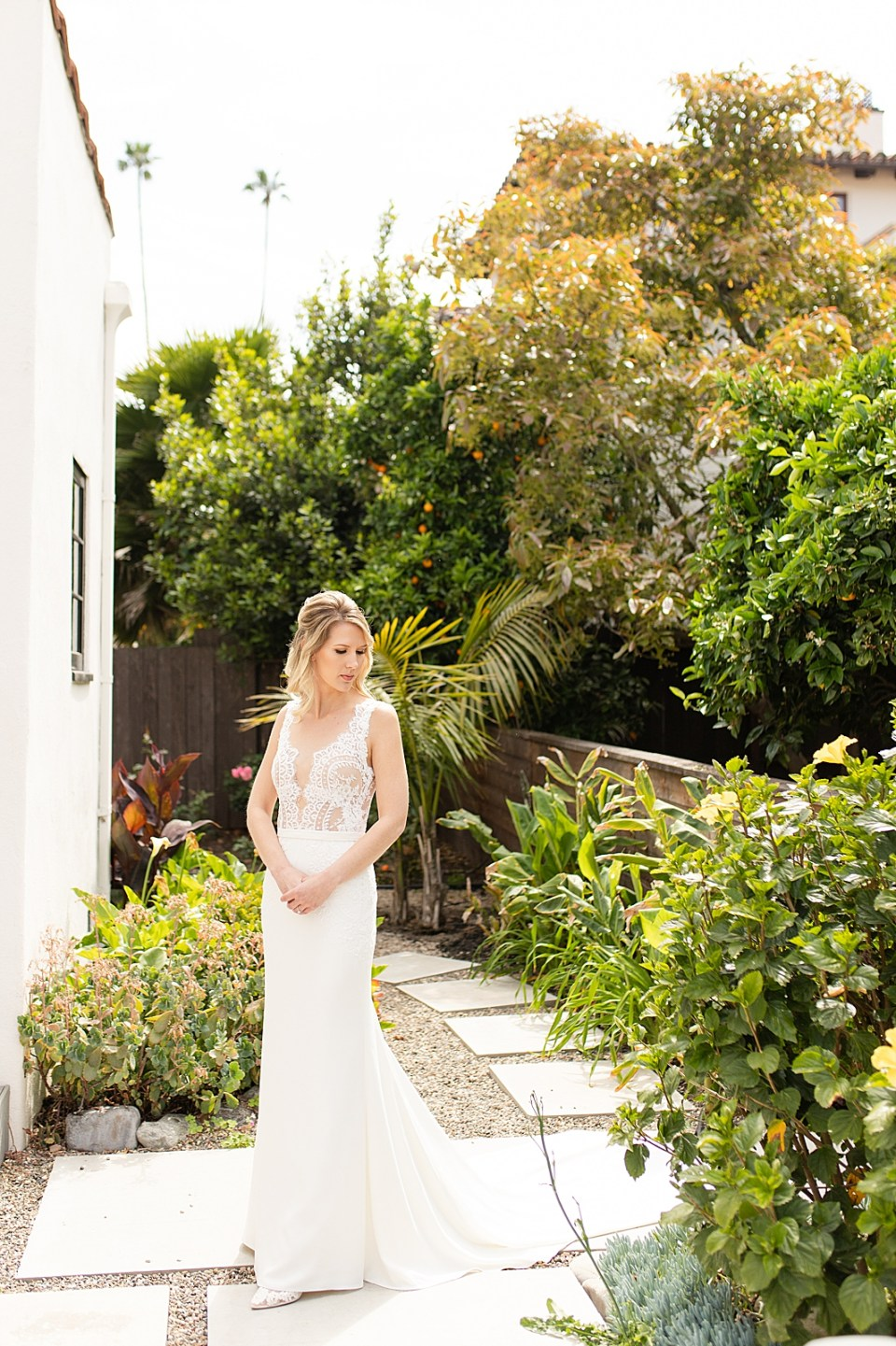 A photo of the bride smiling over her shoulder outside behind their Air BnB before her Villa & Vine Wedding
