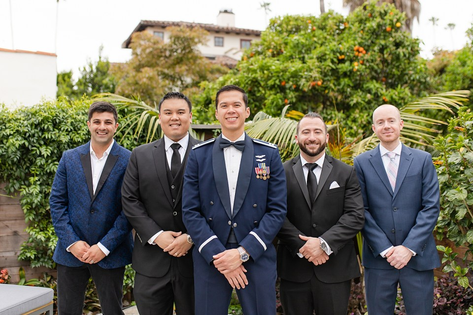 The groom with his best man and friends smiling at the camera with their hands left over right.