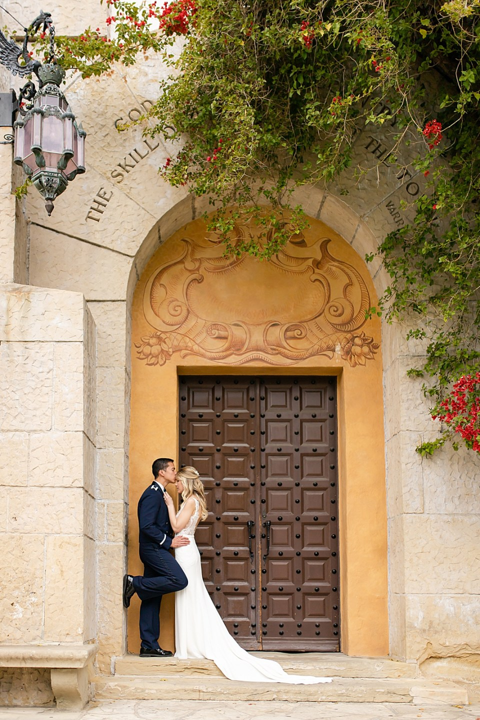 The groom leaning against a wall and pulling his wife to him and kissing her on the forehead.