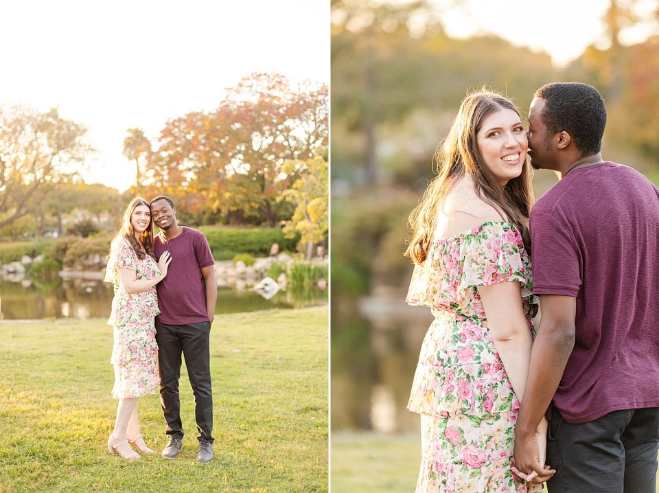 Sarah wearing a floral dress that cuts right before her knee and myles wearing dark gray pants and a maroon shirt. The couple is cuddling closely together with the grass, trees, and the pong behind them.